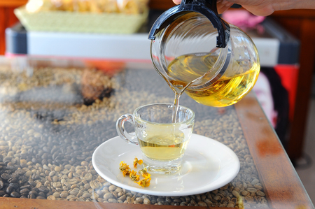 Pouring Chinese Chrysanthemum Tea out of glass jar