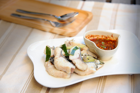 fish food: Boiled fish with Thai Spicy Sauce place on plate (still life style)