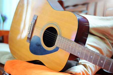 accoustic guitar resting against a sofa (Style Still Life)