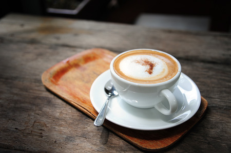 hot coffee cappuccino in cup on table (style still life)