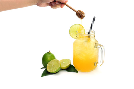 lemon slices and hand pouring honey bee on lemon juice in glass