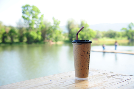 iced coffee on wood table and nature background