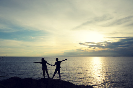 Silhouette Couple in love Standing on the rocks by the sea. (Style Still Life)
