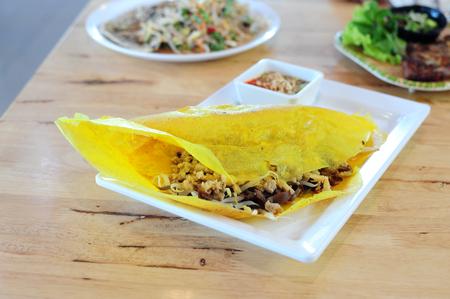 Vietnamese stuffed crispy omelette on wood table Standard-Bild