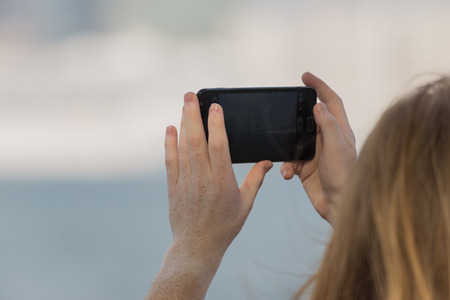 zoomed in: Zoomed Redhead Man taking Pictures in Pier of Hong Kong Island
