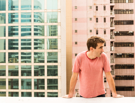 corbel: Man climbing a Corbel of a Rooftop on Hong Kong Island Stock Photo