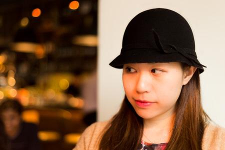starring: Cute Asian Girl starring at somewhere in a Bar in Hong Kong Island