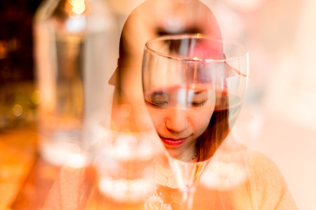 Reflection of a face on a red wine glass in a modern Bar