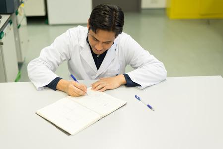 laboratorio: Escritura hermosa del investigador en su laboratorio-libro en Laboratorio de Química Foto de archivo