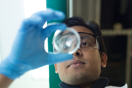 iluminated: Researcher holding an iluminated Petri Dish in Biochemistry Lab