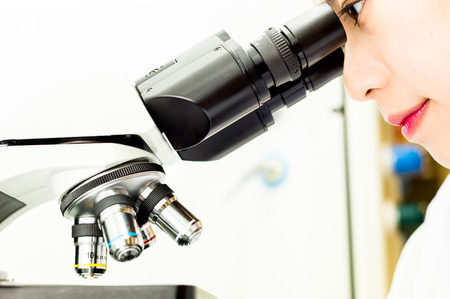 microscope lens: Asian Researcher looking through a Microscope Lens in a Biochemistry Lab Stock Photo