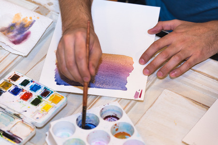 art school: Hands mixing Water Colors in a painting Class