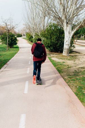 park path: Guy moving with his Skate on a Park Path