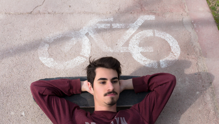 skater boy: Resting on a Bike Path in a Sunny Day