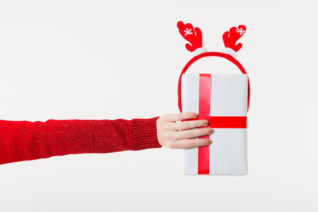 Hand without Gloves holding a Present on a white Background