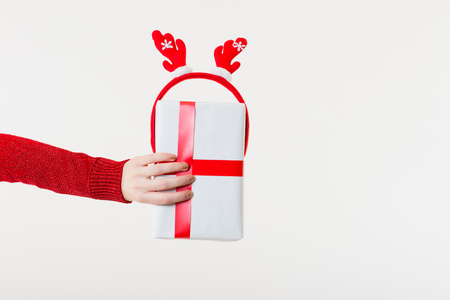 christmastide: White Background: Hand without Gloves holding a Present Stock Photo