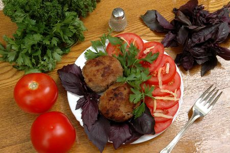verdure: roasted cutlets with tomato and verdure on wooden table