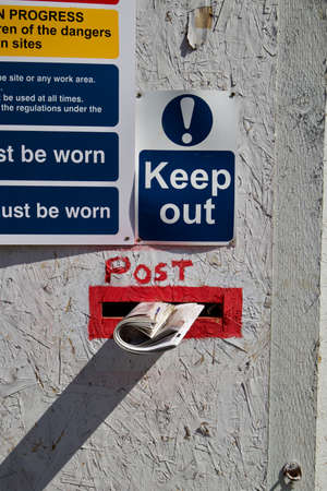 Close up of a door with a post box and newspaper and keep out sign
