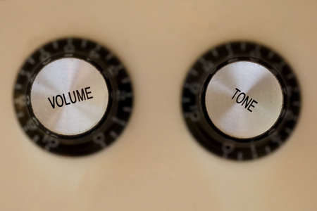 Top down close up shot of volume and tone guitar knobs
