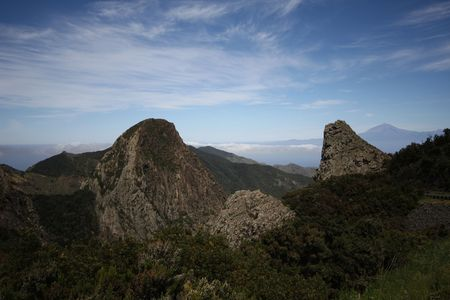 wide angle lens: Ojila and Carmona rocks are located in La Gomera island in Canary Islands.They are very famous in that island.Also in background you can see Teides peak in Tenerife.The photo was made with wide angle lens. Stock Photo
