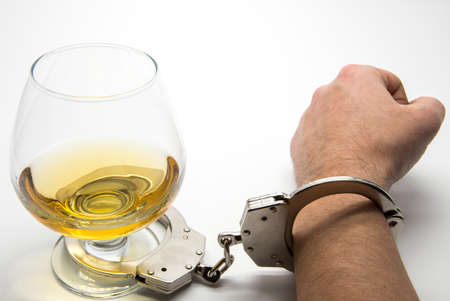 sobriety test: Alcohol and handcuffs - alcohol addiction concept Stock Photo