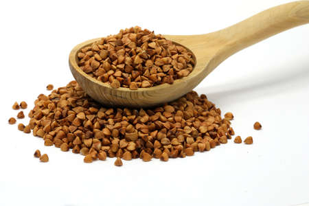 kasha: Buckwheat grains in wooden spoon on white isolated background