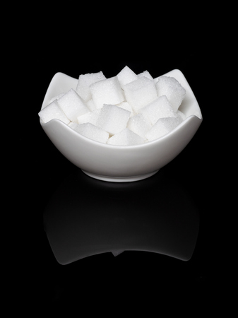 Cube sugar, sugar cubes in an angular shell in front of black background, with mirroring