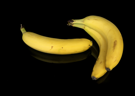 Three bananas on a black background with mirroring