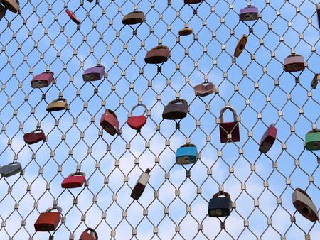 Many padlocks of lovers hanging on bridge railings against blue sky