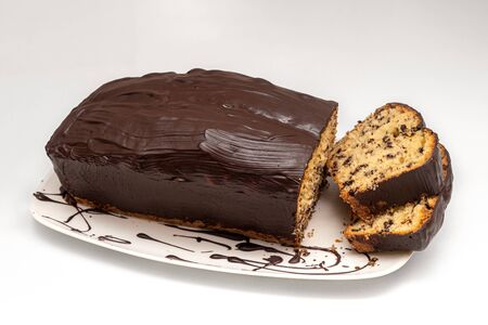 Sponge cake, pot cake or also called box cake with chocolate sauce, sliced. Reklamní fotografie