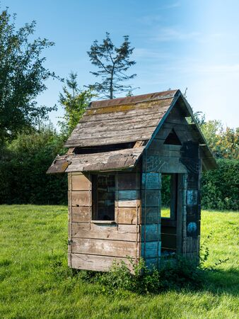 Old, dilapidated playhouse for children on a meadow.