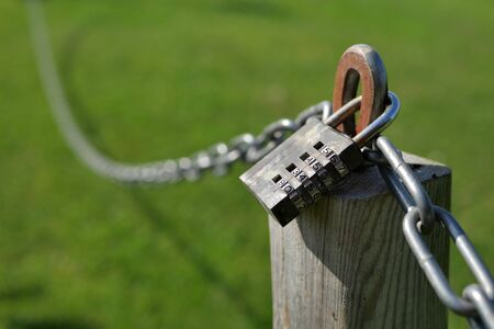 Combination lock secures a chain attached to a wooden post.