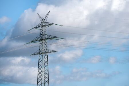 High voltage pylon with four support arms each photographed against a blue sky