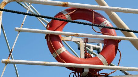 Red lifebuoy attached to a ship railing.