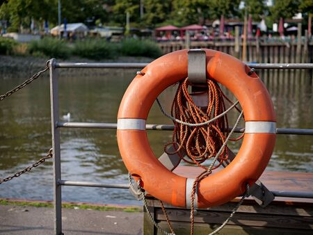 Lifebuoy attached to the harbor wall on a metal railing. Stock fotó