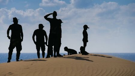 Sand dune by the sea, group of people as a silhouette. Composing
