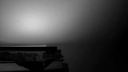 A small stack of old books with an electronic e-reader positioned on top illustrating technological change. Black & white background with dramatic lighting.