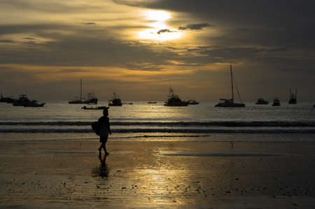 Local male surfer walking on playa San Juan del Sur at with a surf board under his arm. Boats in the back ground. Surfing travel beach sunset.