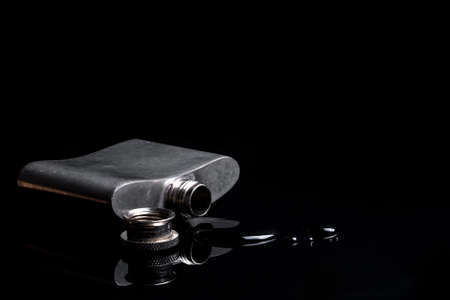 Small worn metallic hip flask spilled over on a dark reflective surface. Drinking metalic liquid isolated alcohol flask