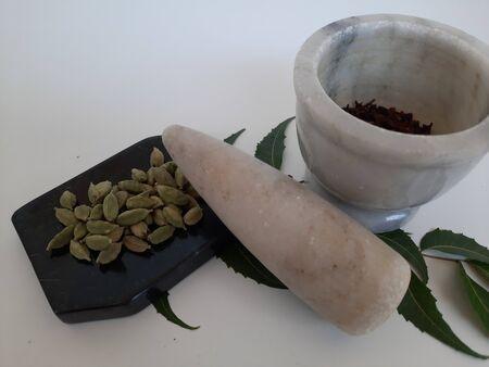 Neem leaves in Mortar Grinder drug and ingredient herbs on plain white background