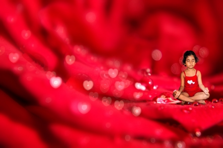 gild child meditating on macro red rose flower  abstract bokeh background photo