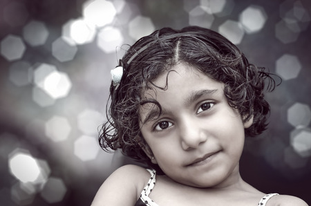portrait of smiling girl child at night with bokeh colorful background photo