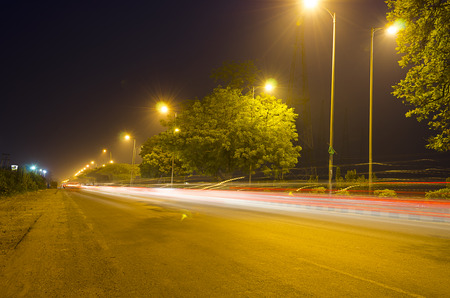 road scene of traffic moving at night with colorful light trails   photo