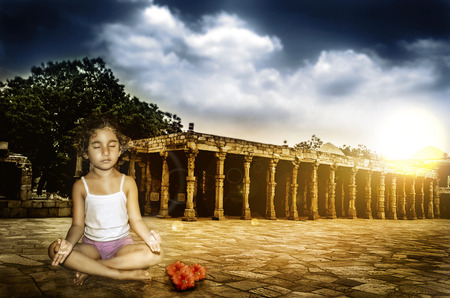 girl child meditating at sunset sunrise with dramaticl sky  photo