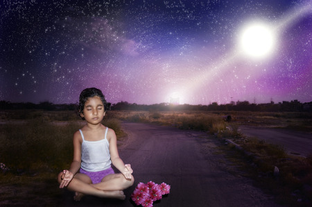 girl child meditating at night with milkyway stary colorful sky  Stock Photo