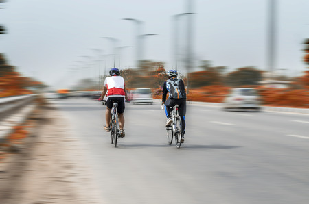 peddle: two persons cycling on road with tanning motion effect Stock Photo