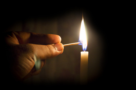 eliminating: hand lighting candle with match stick concept of eliminating dark Stock Photo