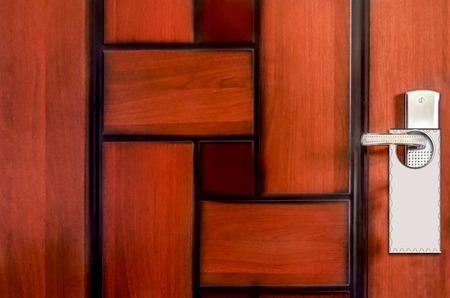 Empty label on abstract unique wooden pattern hotel door handle  photo