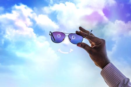 lense: hand holding sunglass watching future through lense or glass