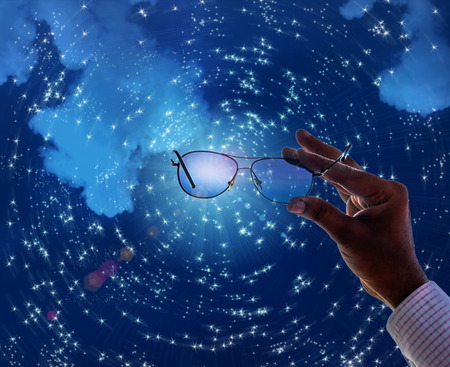 lense: hand holding sunglass watching future through lense or glass on starry night concept